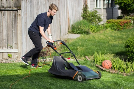 Teen mowing the lawn with an electric lawnmower